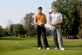 Portrait of young men standing with golf sticks on golf course Royalty Free Stock Image