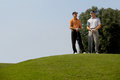 Portrait of young men standing with golf sticks on golf course Stock Image