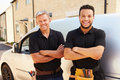 Portrait of a young and a middle aged tradesman by their van Royalty Free Stock Photo