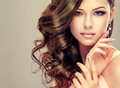 Portrait of young model with wavy dense hair silver lipstick and french style manicure Royalty Free Stock Photography