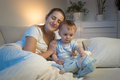 Portrait of young mother lying in bed with her baby boy at night Royalty Free Stock Photo