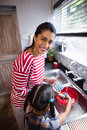 Portrait of young mother standing by daughter working in kitchen Royalty Free Stock Photo