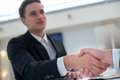 Portrait of young and motivated confident businessman shaking hand agreement with a handshake successful businessmen is to his Stock Images