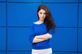 Portrait of young naughty beautiful brunette woman with blue geometric background Royalty Free Stock Photo