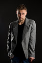 Portrait of young negligent man on dark studio background Stock Photos