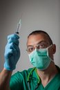 Portrait of a young physician with surgical mask in green uniform Royalty Free Stock Images