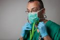 Portrait of a young physician with surgical mask in green uniform Stock Images