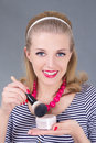 Portrait of young pinup woman with make up brush and powder over grey Stock Photography