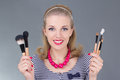 Portrait of young pinup woman with make up brushes over grey Stock Image