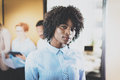 Portrait young pretty african american businesswoman standing in front of co-workers in modern office. Horizontal Royalty Free Stock Photo