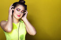 Portrait of young pretty girl with colourful artistic make-up and updo hair listening to the music in headphones and smiling Royalty Free Stock Photo