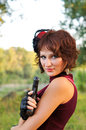 Portrait of a young pretty girl with gun on nature Stock Image