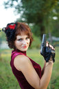 Portrait of a young pretty girl with gun on nature Stock Images