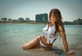 Portrait of young sexy brunette girl in white bikini and wet t shirt at the beach sensual attractive woman water wearing Stock Photos