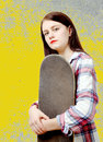 Portrait of young skater girl holding a skateboard Royalty Free Stock Photo