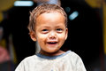 Portrait of a young smeared sherpa boy smiling in Nepal.