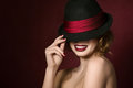 Portrait of young smiling actress beautiful holding black hat with red ribbon over dark red background Stock Images