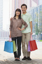 Portrait of young smiling couple going shopping and holding colorful shopping bags in the street looking at camera beijing chi Stock Images