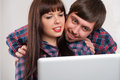Portrait of young smiling couple using laptop at home while sitting Royalty Free Stock Image