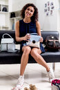 Portrait of young smiling female shopper sitting with a new handbag on her laps in accessories shop Royalty Free Stock Photo