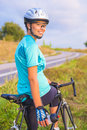 Portrait of young smiling happy female caucasian cyclist athlete on bicycle having a water break vertical image Royalty Free Stock Photo