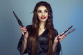 Portrait of young smiling model with perfect teeth and long hair wearing silk peignoir holding curling wand and hair straightener Royalty Free Stock Photo