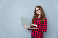 Portrait of young smiling woman standing and holding laptop Royalty Free Stock Photo