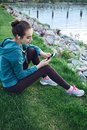 Portrait of young and sporty woman in sportswear sits with the smartphone on the grass in park