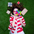 Portrait of a young styled redhead woman with pinwheel toy present around lying down on green spring grass, above point of view Royalty Free Stock Photo