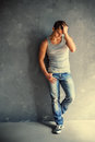Portrait of young stylish man full length wearing undershirt and jeans leaning to gray textured wall Royalty Free Stock Photography