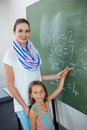 Portrait of young teacher assisting girl writing on chalkboard
