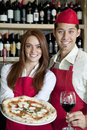 Portrait of a young wait staff with wine glass and pizza Royalty Free Stock Photo