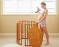 Portrait of young white Caucasian happy woman assembling wooden baby crib in nursery at home Royalty Free Stock Photo