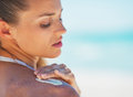 Portrait of young woman applying sun screen creme on beach Royalty Free Stock Images