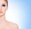 Portrait of a young woman in beautiful makeup and attractive naked caucasian the image is taken on light blue background Stock Images