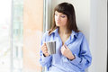 Portrait young woman blue shirt drinking coffee looking out window Royalty Free Stock Photography