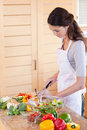 Portrait of a young woman chopping pepper Royalty Free Stock Photos