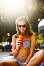 Portrait of young woman with cocktail glass chilling in the tropical sun near swimming pool on a deck chair with palm Royalty Free Stock Photo