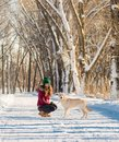Portrait of a young woman with dog on winter walk.