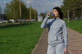 Portrait of young woman drinking water outdoor. Sport fitness female runner after jogging.