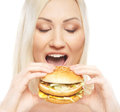 Portrait of a young woman eating a cheeseburger Stock Photography