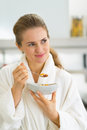 Portrait of young woman eating muesli in kitchen Royalty Free Stock Photo