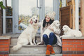 Portrait of the young woman with favourite dogs beautiful girl brunette a long straight hair and gray eyes in a white jacket and a Stock Photos