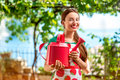 Portrait of a young woman gardener with apron and watering can in the garden Royalty Free Stock Images