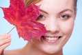 Portrait of young woman girl with red maple leaf skincare habits as symbol capillary skin on blue face taking care her dry Royalty Free Stock Photography