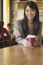 Portrait of young woman holding coffee cup in a coffee shop, Beijing Stock Photo