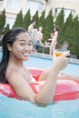Portrait of young woman holding a drink and sitting on an inflatable tube in the pool Royalty Free Stock Photo