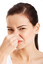 Portrait of a young woman holding her nose because bad smell isolated on white Stock Photos