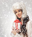 Portrait of a young woman holding a present and attractive in winter hat the image is taken on light grey snowy background Royalty Free Stock Image