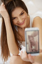 Portrait of a Young Woman Holding a Smartphone Digital Camera an Royalty Free Stock Photo
